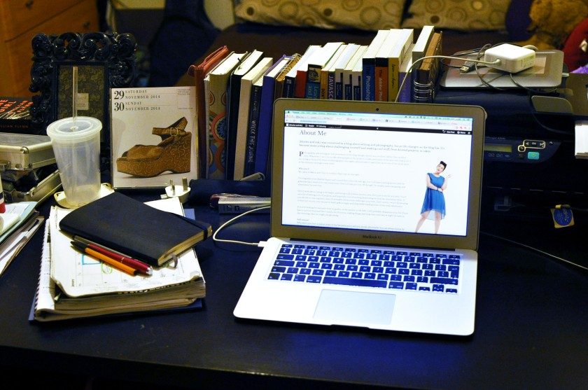 Desk full of books and a laptop