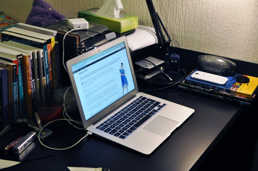 Corner of desk with laptop and comics