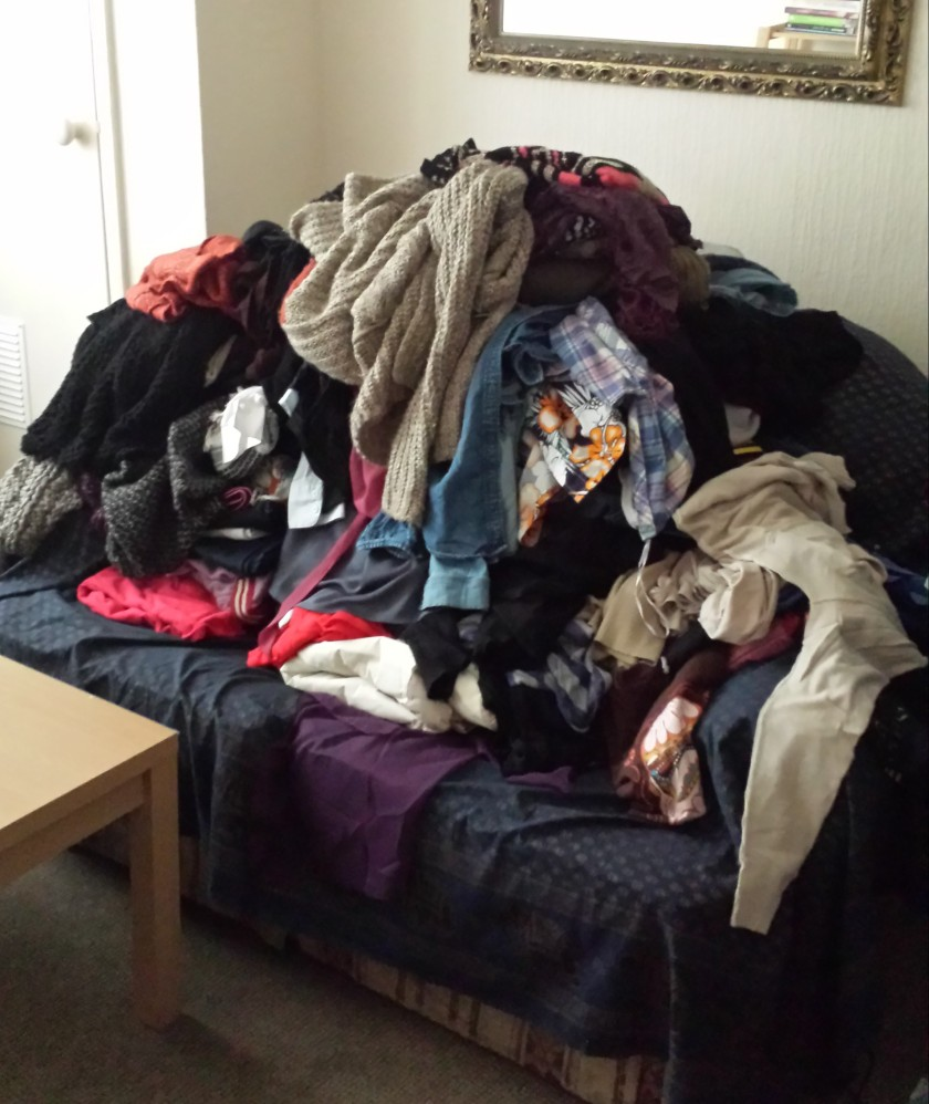 Tops piled up on sofa before being discarded
